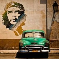 coche verde chocado en pared con imagen revolución